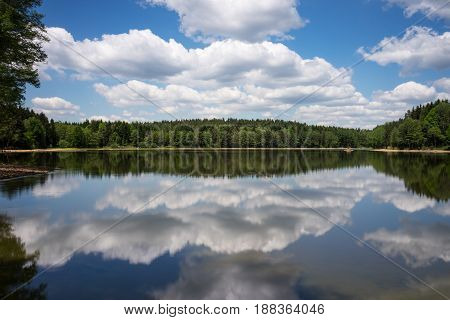 Idyllic Landscape With Lake Reflection lake with forest and cumulus clouds
