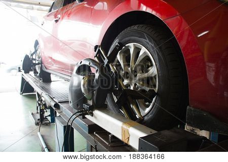 Car mechanic installing sensor during suspension adjustment. Wheel alignment work after change new tire at service station