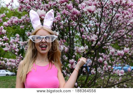 Happy girl or cute woman with bunny ears and funny glasses with long blond hair laughing in pink top at blossoming tree with magnolia flowers in spring park on floral environment. Easter. Springtime
