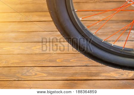 The wheel of a stylish bicycle with a black rim and a black rubber tire red spokes a stylish wooden background