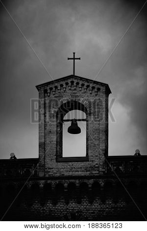 The bell tower of an old church with a hanging bell.