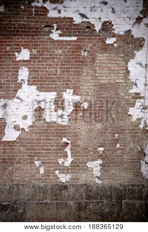 The worn facade of a brick building with peeling paper scraps.
