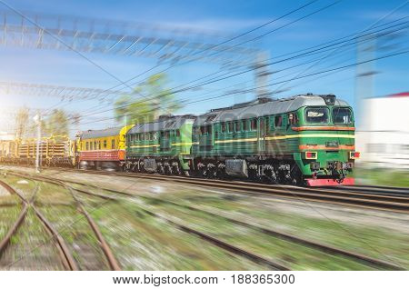 Double freight train green locomotive and on the forks of the railway tracks