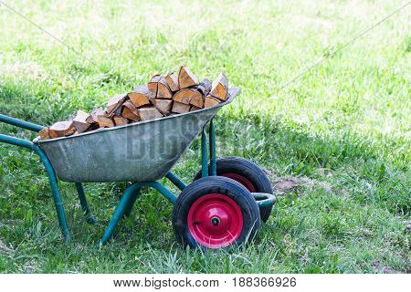 Hand Truck With Neatly-stacked Firewood On The Green Grass In The Garden