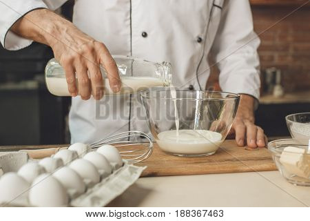 Bakery chef cooking bake in the kitchen professional adding ingredients
