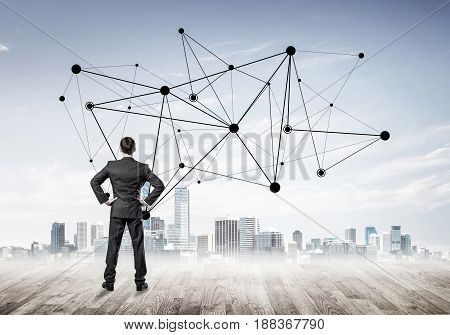Businessman standing with back and looking at network drawn concept