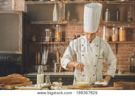Bakery chef cooking bake in the kitchen professional adding flour