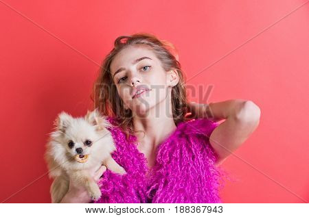 spitz dog pet eat bagel in hands of girl or cute woman with natural blond long wavy hair smiling with closed mouth on young face no makeup in pink feather boa on red wall. Fashion friendship