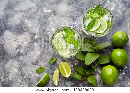 Mojito traditional cuban highball cocktail alcohol drink, top view copy space, summer tropical vacation beverage with rum, peppermint mint, lime juice, soda water, sugar and ice on concrete background