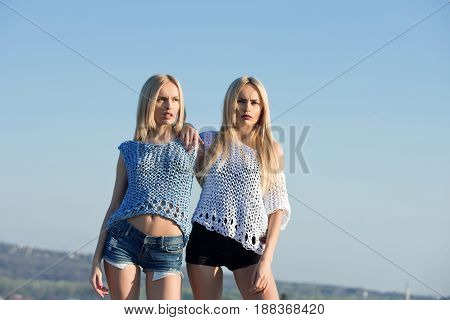 girls or cute twin women stylish female models with long blond hair in fashionable knitted tops and shorts posing on sunny day on blue sky. Idyllic summer vacation. Nature. Wanderlust
