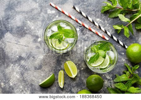 Mojito traditional Cuban cocktail alcohol refreshment drink in highball glass, summer tropical vacation beverage with rum, mint, lime citrus juice, soda water and ice on concrete table. Top view