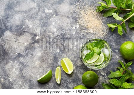 Mojito cocktail alcohol drink top view copy space in highball glass, summer tropical vacation beverage with rum, mint leaves, lime citrus juice, soda water and ice on concrete table.