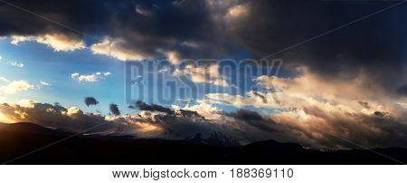 Altai Ukok the sunset over the mountains in cloudy cold weather. Wild remote places no one around. Rain clouds over the mountains