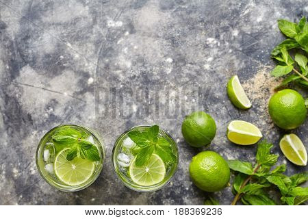 Mojito cocktail non alcohol bar refreshment drink top view copy space two highball glass, summer tropical vacation beverage with rum, citrus slice, mint, lime, soda water and ice on concrete table.