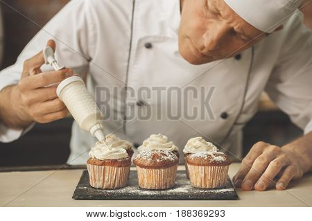 Bakery chef cooking bake in the kitchen professional put cream