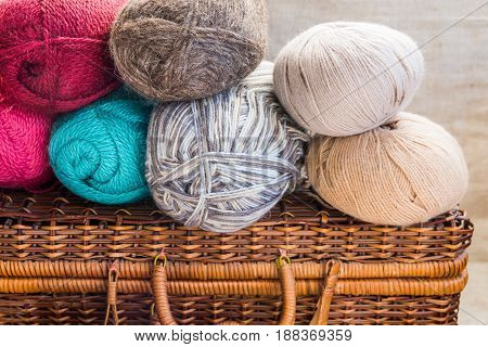 Vintage crafts wicker chest clews balls of multi-color wool yarn red blue white beige grey knitting hobby concept header banner for websites close up