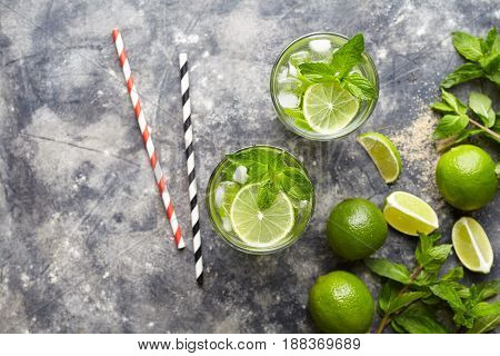 Mojito cocktail traditional Cuba travel vacation drink with rum, ice, mint, lime slices in highball glass on concrete table background, top view