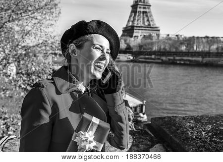 Woman In Paris Using A Cell Phone And Holding Present Box
