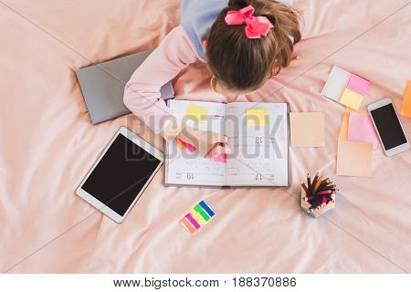 Young teenager girl alone at home childhood writing in planner