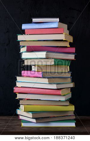 Stack of books in the colored cover on the table in the background of a school blackboard.