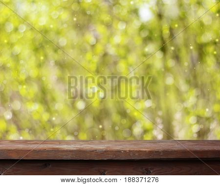 Empty wooden table on spring blurred background with bokeh. Empty space for Your subject.