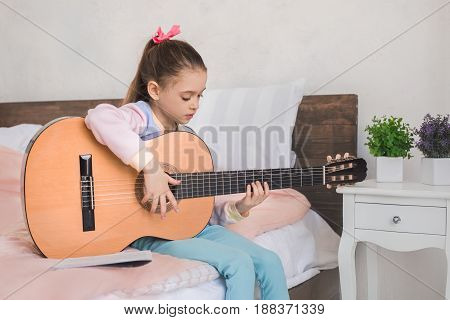 Young teenager girl alone at home childhood playing guitar