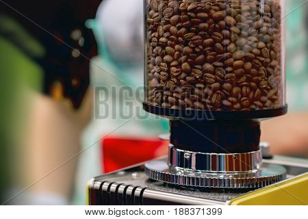 Close-up fresh roasted coffee beans in a grinder for prepare to milling and metal millstones. Concept of tasty aroma coffee culture, service and catering