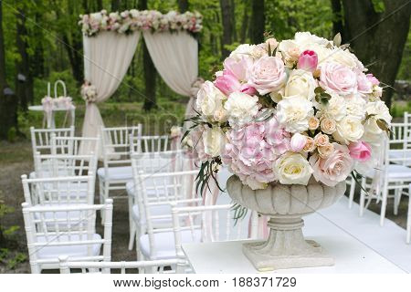 Beautiful bouquet of roses, peonies and tulips in stone vase in front of wedding arch and lined up chairs