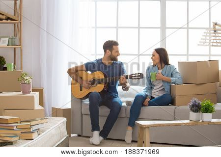 Young couple man and woman moving to a new apartment together relocation playing guitar