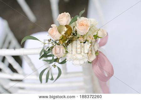 Pink ranunculus and roses buds in tenderless boutonniere with pink bow, closeup