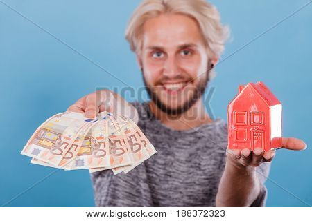 Household savings and finances economy concept. Smiling man holding money and piggy bank in the shape of a house studio shot on blue background