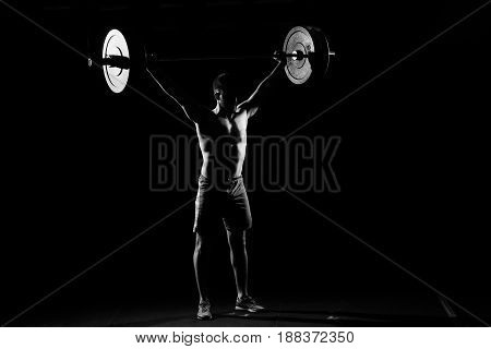 Fitness training. Man standing with barbell in dark gym.