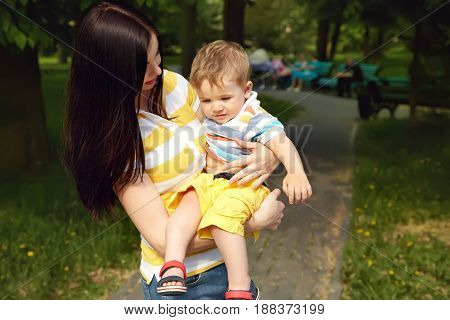 sad tired child and mom walk in the summer park. mother and son
