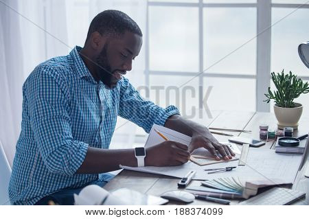 Young african male working in the office business architect drawing project