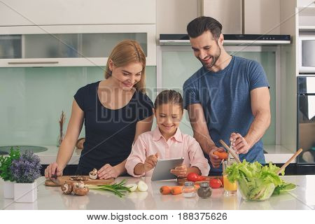 Young family cooking lunch meal together in kitchen daughter showing tablet