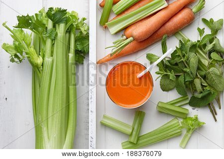 Carrot and celery juice with fresh vegetables and herbs in white wooden tray top view