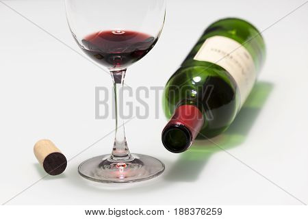 Cup with some red wine cork and empty bottle
