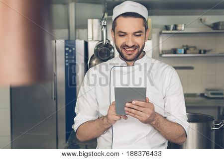 Male japanese restaurant chef working in the kitchen using digital device