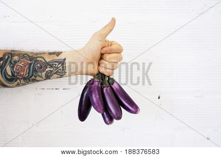 Close up view on man hand with tattoos and thumb up holding bunch of little fresh purple bright eggplants in tight fist on white bricks wall background.