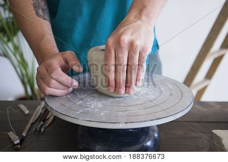 Sculptor in blue t-shirt makes pot with piece of grey raw clay on pottery sculpting wheel on wooden dark brown table with tools white background with big green plant. Close up view on hands.