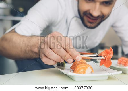 Male japanese restaurant chef cooking in the kitchen adding ingredients