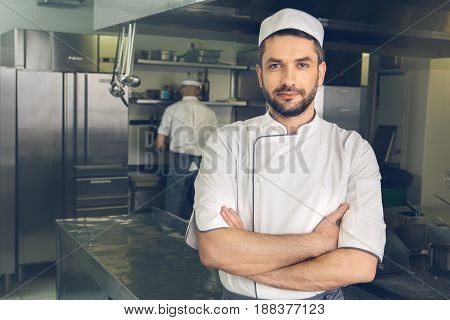 Male japanese restaurant chef cooking in the kitchen standing confident