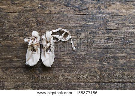Old ballet shoes on old wooden floor. Pink ballet pointe.