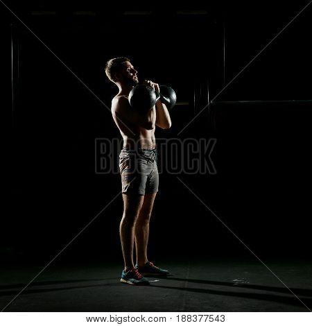 Fitness training. Man doing exercises with weights in dark gym.