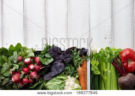 Fresh vegetables and herbs in wooden box on white table, copyspace