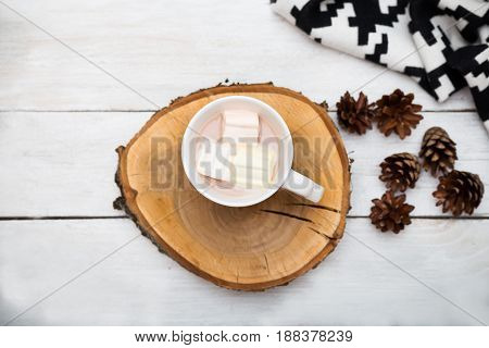 White cup with hot chocolate and marshmallows on a white wooden background. flat lay