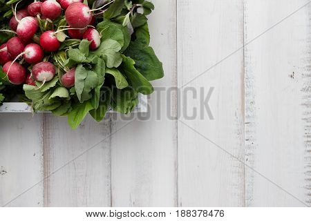 Fresh radish in wooden box on white table, top view