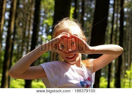Young attractive girl in park shows hands of heart