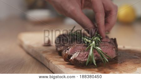 man decorating sliced medium rib eye steak with rosemary branch, wide photo