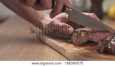 man slicing cooked medium rib eye steak on board, wide photo